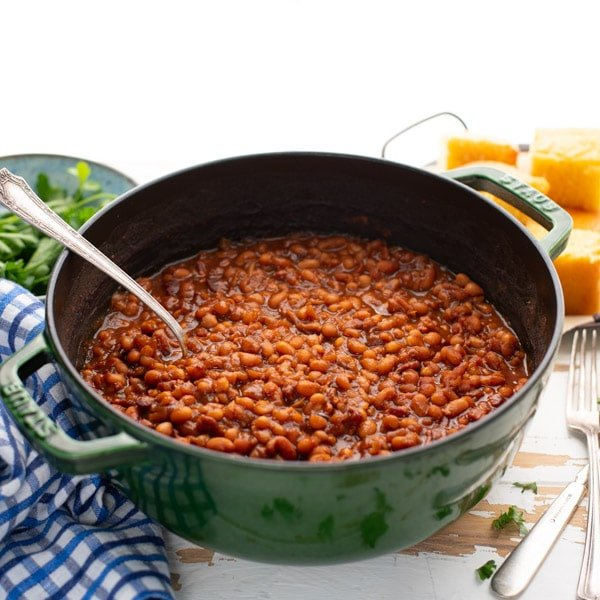 Square image of a green Dutch oven full of Boston baked beans