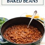 Side shot of a green Dutch oven full of homemade baked beans with bacon and text title box at top