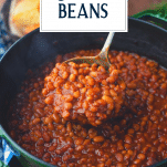 Close up shot of a ladle full of boston baked beans with text title overlay