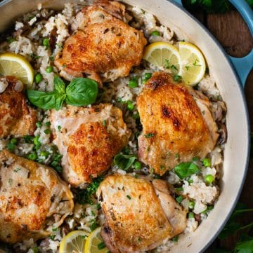 Overhead image of one pot chicken and rice with mushrooms and peas in a Dutch oven