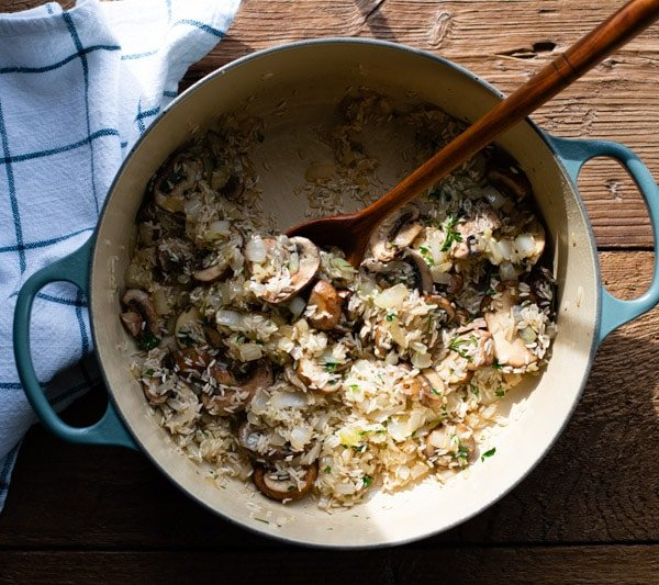 Stirring rice with mushrooms and onions in a Dutch oven