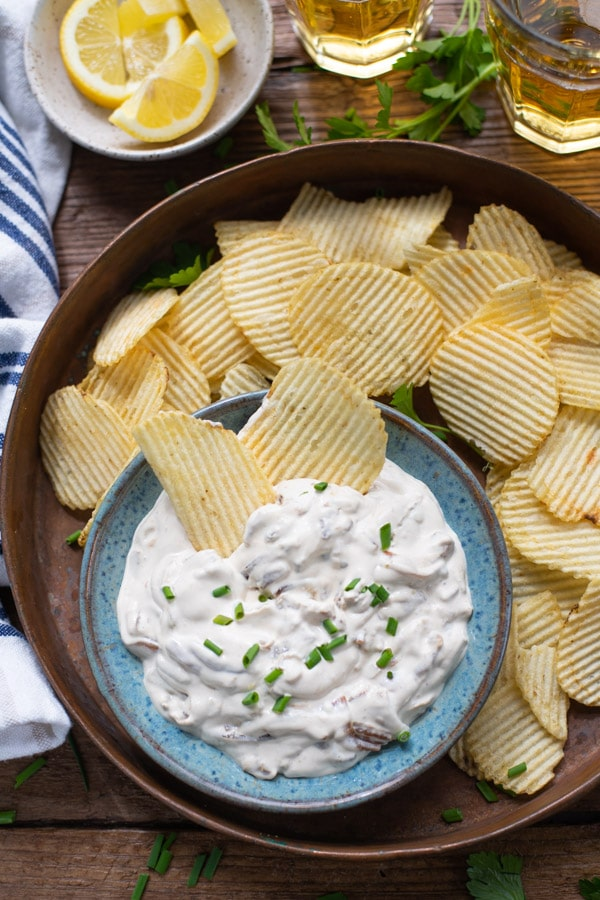 Close up overhead shot of onion dip from scratch with potato chips and fresh chives