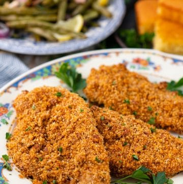 Close up side shot of a platter full of oven baked pecan crusted chicken