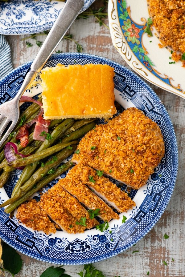 Close overhead image of a sliced pecan chicken breast on a plate with cornbread and green beans