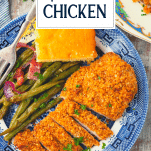 Plate of pecan crusted chicken with sides and a text title overlay