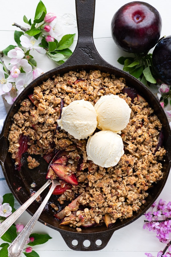 Overhead shot of plum crisp with ice cream on top and flowers nearby