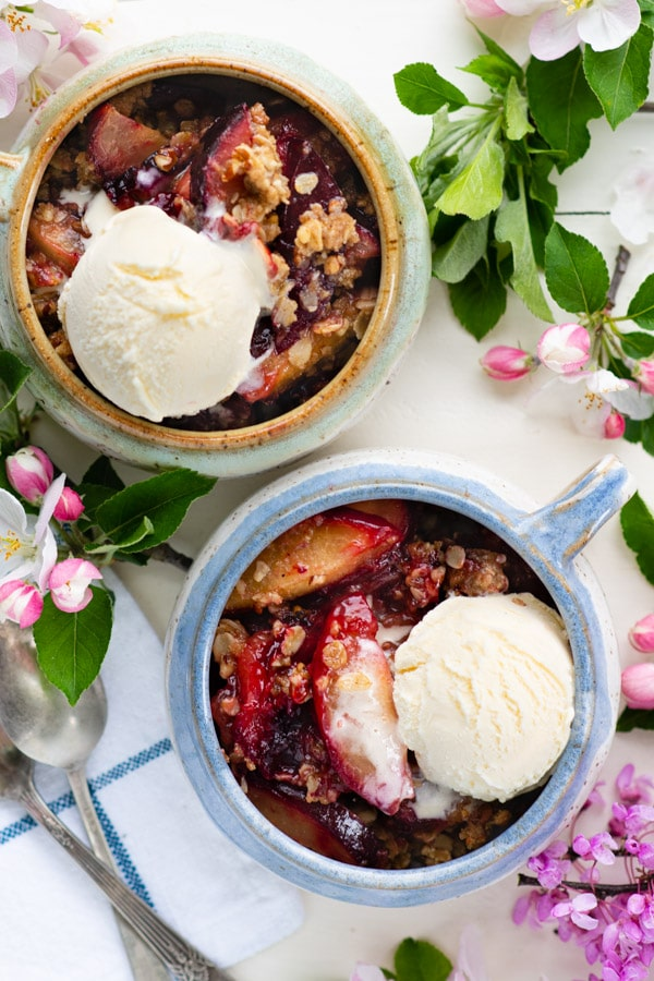 Overhead shot of two bowls of warm plum crisp on a white table surrounded by flowers