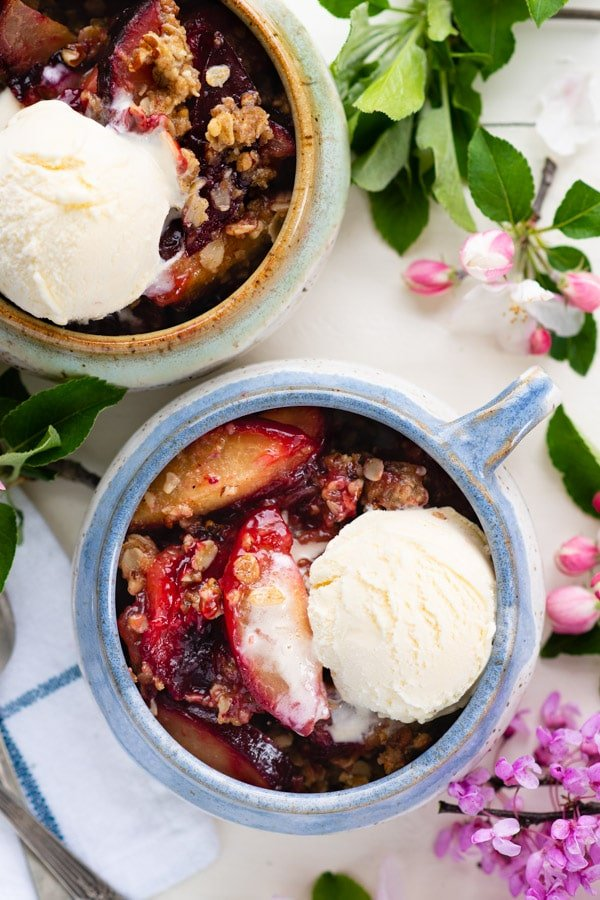Overhead shot of two bowls of easy plum crisp recipe with ice cream on top