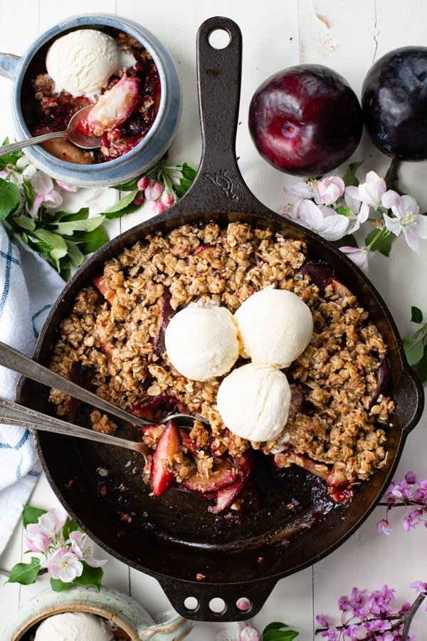Overhead shot of plum crisp on a white table with vanilla ice cream on top