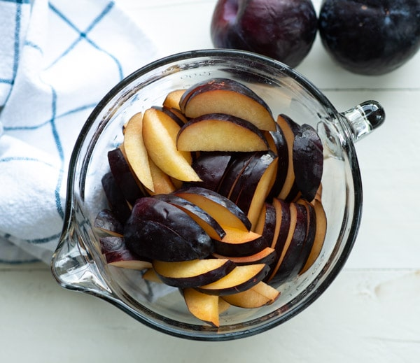 Bowl of sliced fresh plums