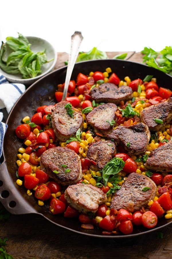 Side shot of a skillet of pork medallions with corn and bacon and tomatoes