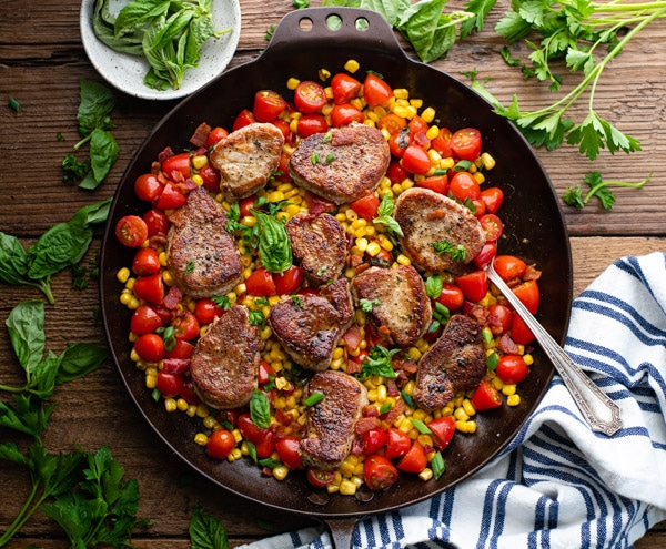 Horizontal overhead shot of a pan of seared pork medallions recipe with corn and tomatoes