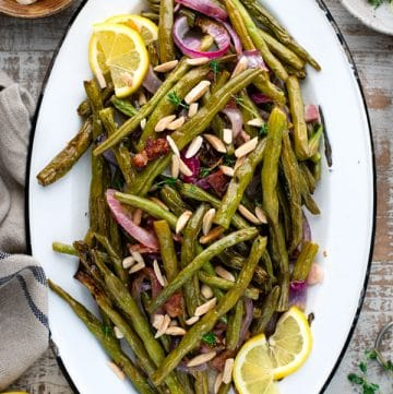 Overhead platter of roasted green beans with bacon and herbs on a white surface