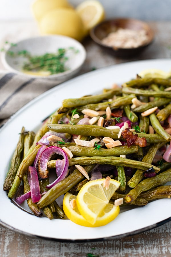 Side shot of oven roasted green beans on a white serving tray with bacon and almonds