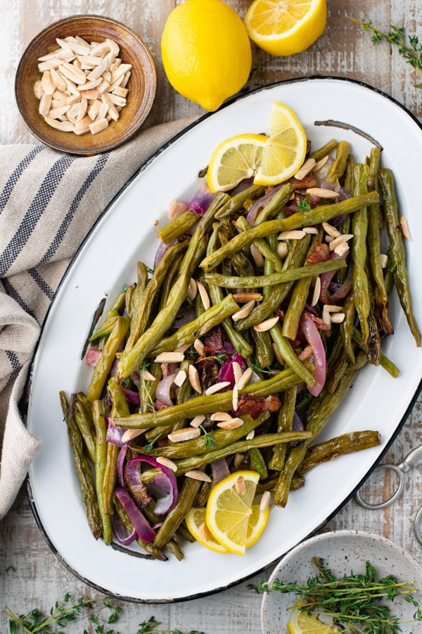 Overhead shot of crispy roasted green beans with bacon and lemon