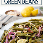 Side shot of oven roasted green beans on a white platter with text title box at top