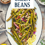 Overhead shot of a platter of roasted green beans with bacon and herbs and text title overlay