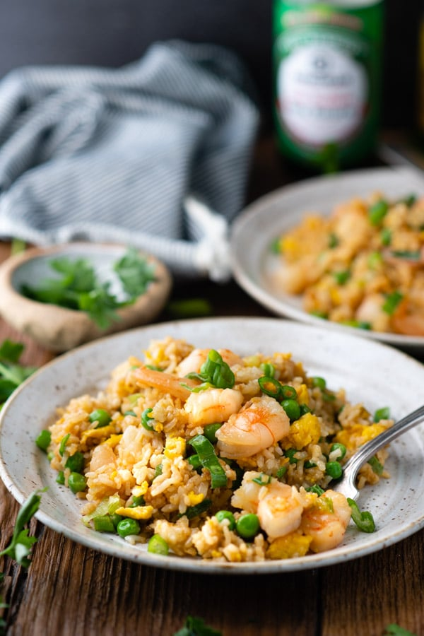 Front shot of two plates of easy shrimp fried rice on a wooden table