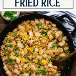 Overhead shot of a skillet of shrimp fried rice recipe with text title box at top