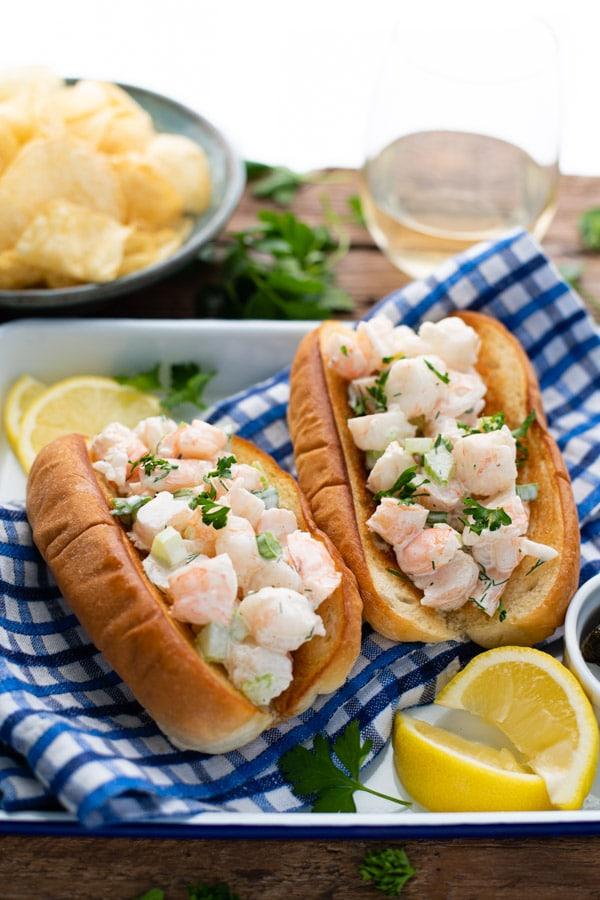 Front shot of shrimp rolls on a serving platter with a side of lemon