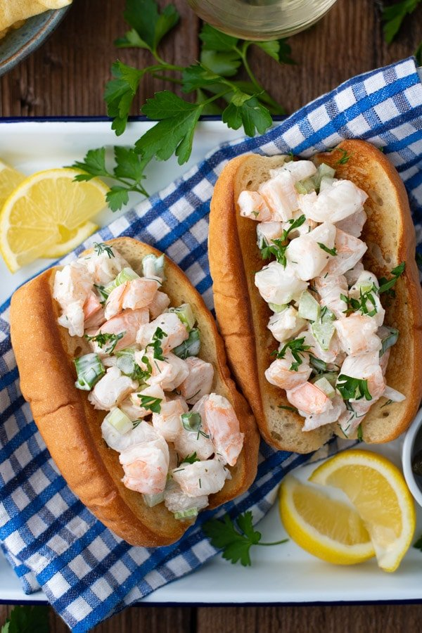 Overhead shot of two New England shrimp rolls on a platter with a blue and white checked cloth