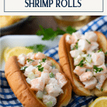 Front shot of two shrimp rolls on a plate with a text title box at the top
