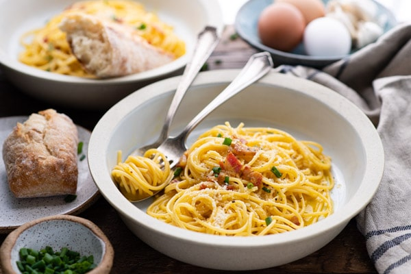 Horizontal shot of two bowls of authentic spaghetti carbonara on a table
