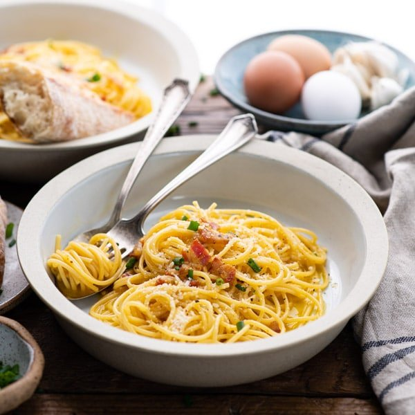 Square image of a bowl of simple spaghetti carbonara on a wooden table