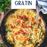 Zucchini au gratin in a cast iron skillet with text title overlay