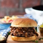Front shot of a shredded beef bbq sandwich on a wooden cutting board