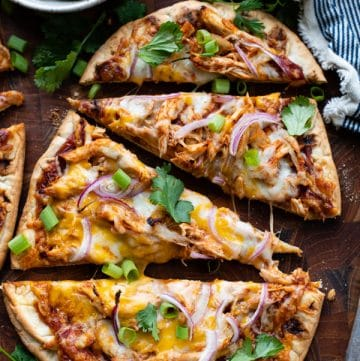Close overhead shot of bbq chicken flatbread pizza sliced on a wooden cutting board