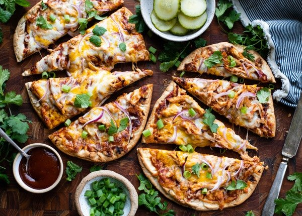 Two homemade bbq chicken pizzas on a cutting board