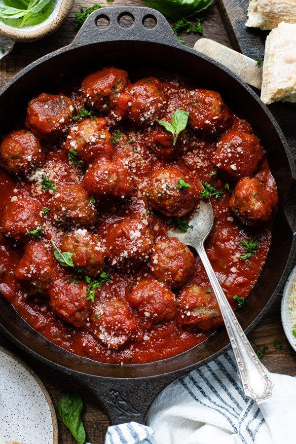 Close overhead image of a spoon in a skillet of oven baked meatballs with sauce