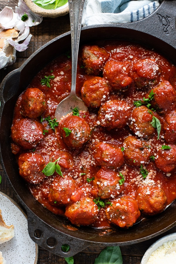Close up overhead shot of baked meatballs in a cast iron skillet