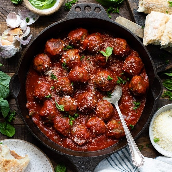 Square image of baked Italian meatballs in a cast iron skillet