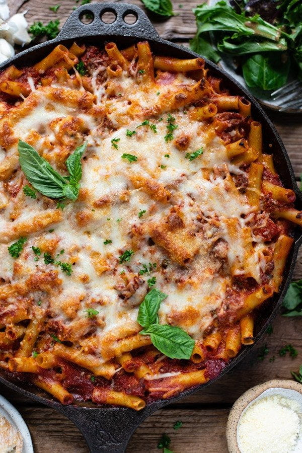 Close overhead image of baked ziti with ricotta and sausage in a cast iron skillet on a wooden table