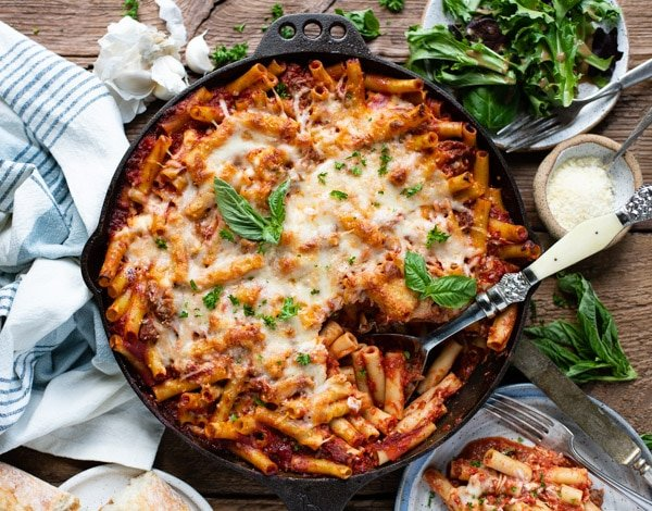 Horizontal overhead image of a pan of the best baked ziti recipe with sausage, ricotta and fresh herbs.