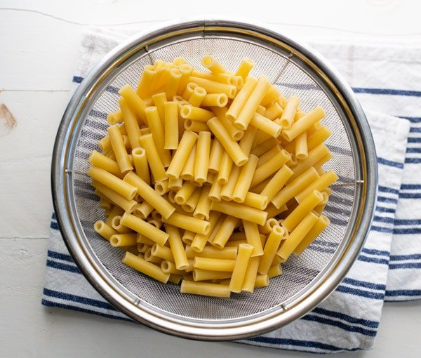 Ziti pasta draining in a colander