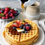 Pouring syrup on a plate of crispy Bisquick waffles with fresh berries