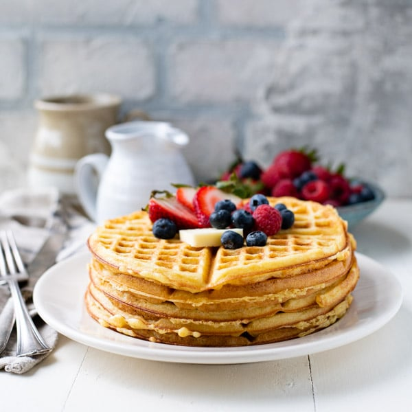 Square image of a plate of homemade waffles with fresh fruit on top