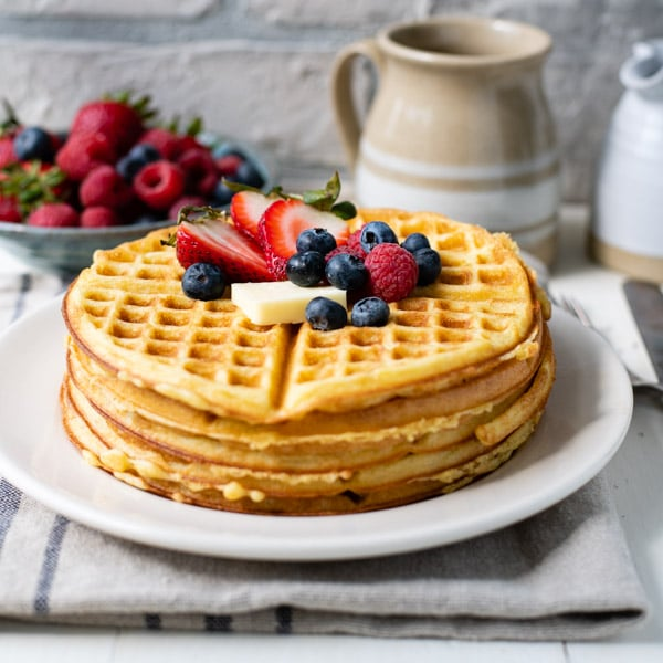 Square side shot of a stack of crispy waffles on a plate
