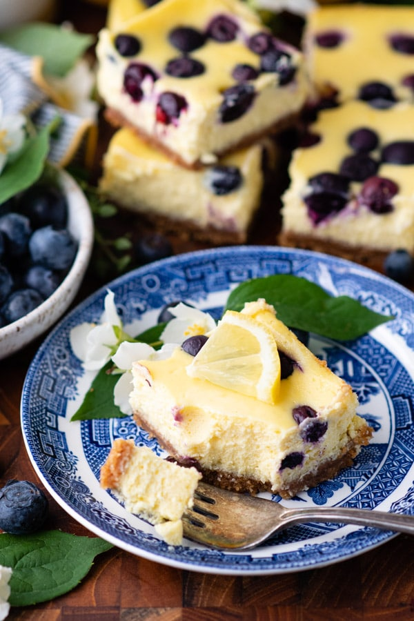 Lemon cheesecake square with blueberries on a blue and white plate with a fork