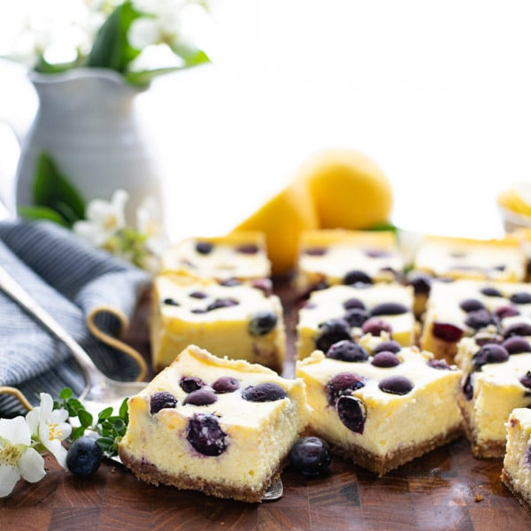 Square side shot of easy cheesecake bars on a wooden cutting board with a server
