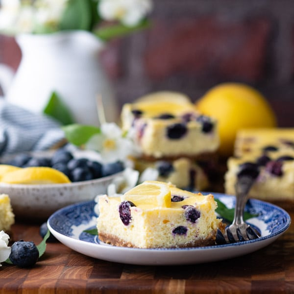 Square image of a lemon blueberry cheesecake cookie bars on a plate