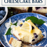Slice of lemon blueberry cheesecake bars on a plate with text title box at top