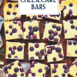 Overhead shot of sliced lemon cheesecake bars with blueberries on a cutting board with text title overlay
