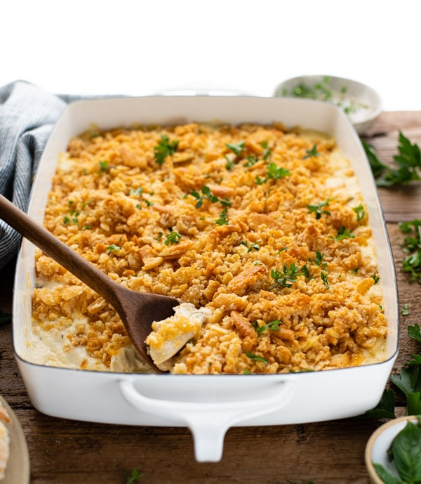 Front shot of cheesy chicken casserole in a white dish with a wooden spoon