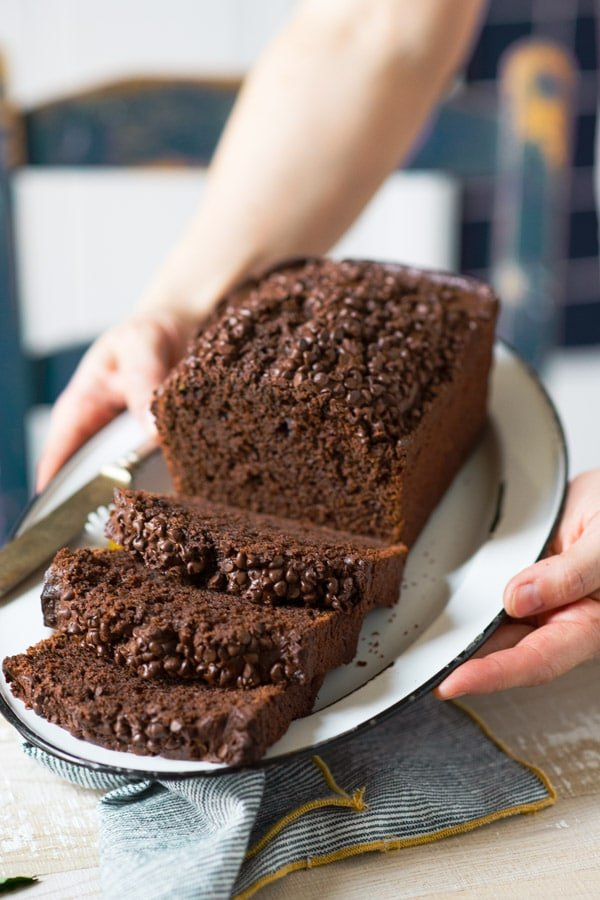 Hands holding a tray of double chocolate zucchini bread with chocolate chips