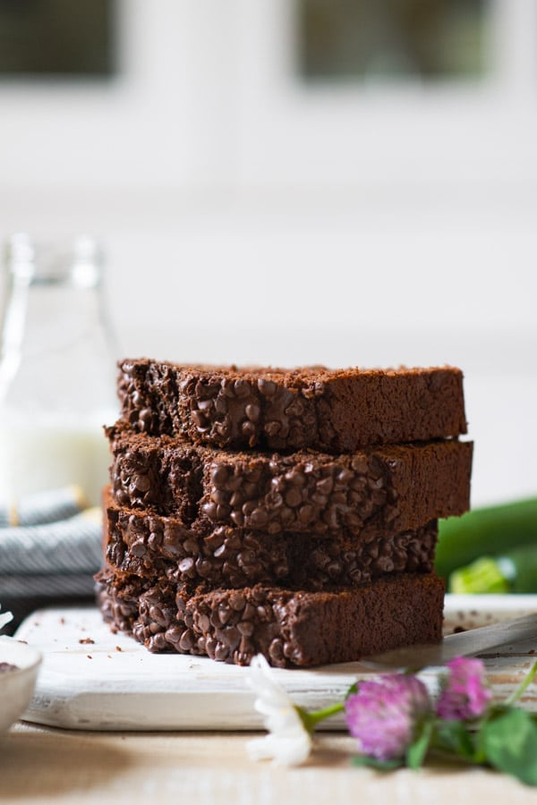 Side shot of the best chocolate zucchini bread stacked on a wooden board with milk in the background