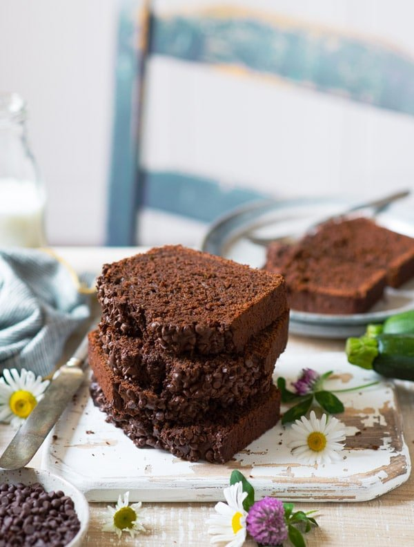 Stack of slices of double chocolate zucchini bread on a white cutting board